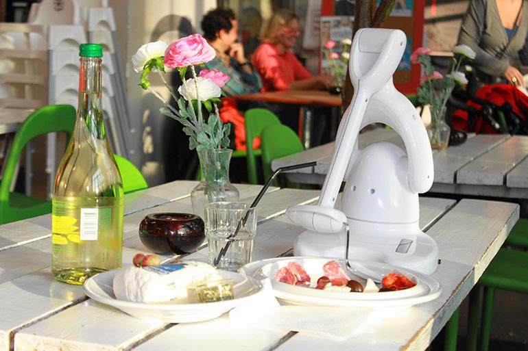 Bestic äthjälpmedel ståendes på ett bord tillsammans med tallrikar med mat
