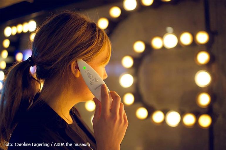 Person med en audioguide mot örat i ABBA The Museum