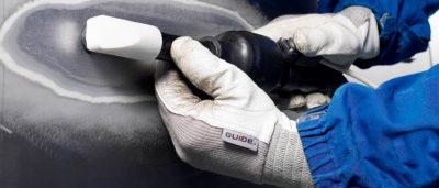 Två händer som håller i en induktionsvärmare mot en bil