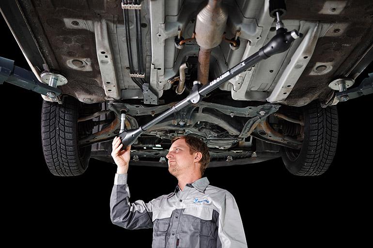 Arbetare under en upphöjd bil med en induktionsvärmare i handen