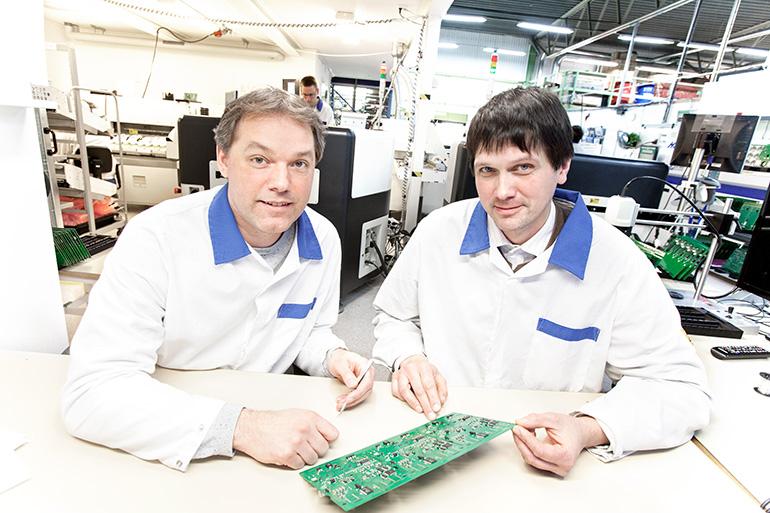 Två EEPAB-medarbetare sittande vid ett bord med ett kretskort