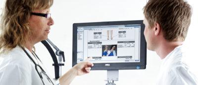 Två personer som kollar på en skärm med resultat från en läkarundersökning